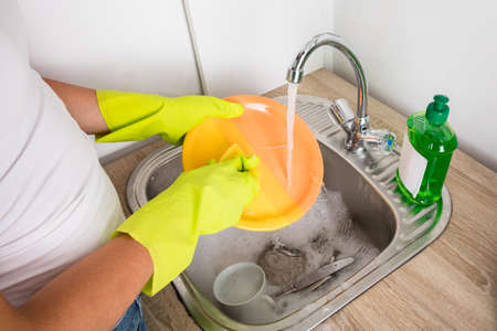 unblock: Close-up Of Person Hand Washing Plate In The Sink At Home