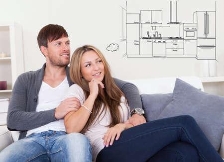 Jeune couple de détente sur Couch Thinking Of Avoir Modern Kitchen dans leur maison