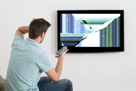 damaged: Frustrated Man Sitting On Sofa In Front Of Television Showing Distorted Screen Stock Photo