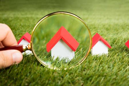 Person Hands Mit Lupe Inspektion Ein Modell Haus Auf Gras Feld Standard-Bild - 69245896