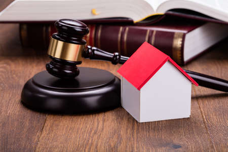 Close-up Of House Model With Gavel On Wooden Table In Courtroom Stock Photo