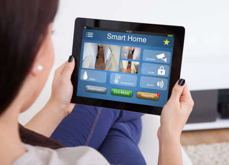 Close-up Of Woman Using Smart Home System On Digital Tablet At Home Standard-Bild