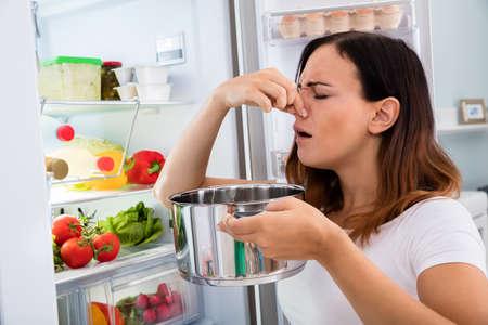 olfato: Mujer joven notado mal olor del alimento zona de Open Frigorífico