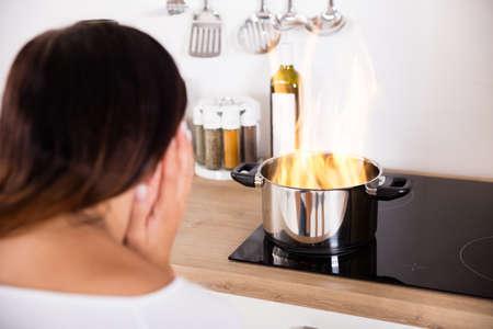 キッチンで調理鍋現代ガスの近くで火事を保持している若い女性に衝撃を与えた