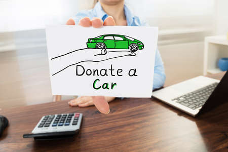 Businesswoman Hand Showing The Concept Of Car Donation On White Paper