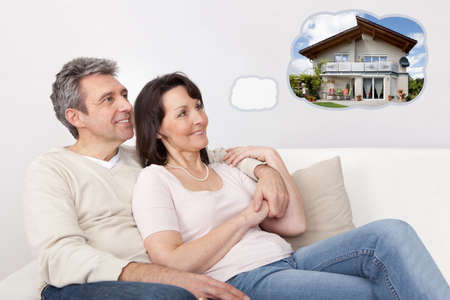 Mature Happy Couple Relaxing On Sofa Dreaming Of Having Their Own House Together