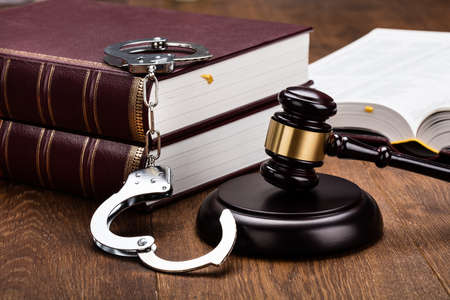 sentence: Gavel And Handcuffs With Red Legal Book On Wooden Table Stock Photo