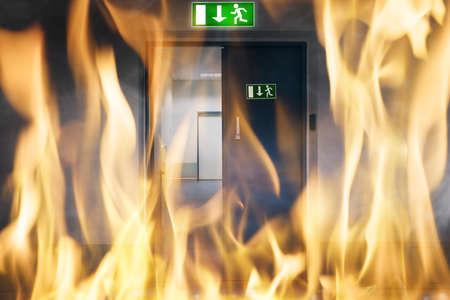 evacuacion: Primer plano de fuego que arde cerca de una salida de emergencia puerta del edificio Foto de archivo