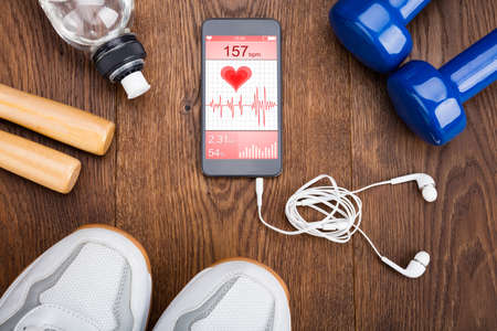 mobile technology: Exercise Equipment With Mobilephone Showing Health Application On Wooden Floor Stock Photo