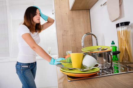 dish: Young Exhausted Woman Standing In The Kitchen Near Utensil In The Sink