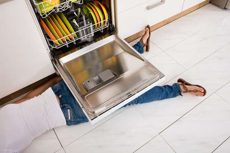 household accident: Close-up Of Young Woman Leg Lying Under A Dishwasher In Kitchen
