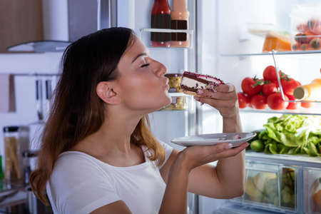 Young Woman Eating Slice Of Delicious Cake In Front Of Open Refrigerator In Kitchen Stock Photo