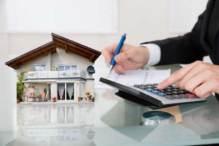 Las extensiones hombre de negocios cálculo usando la calculadora con la casa modelo en el escritorio de oficina