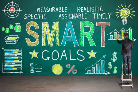 smart goals: Rear View Of Businessperson Standing On Staircase Drawing Smart Goals Concept On Blackboard