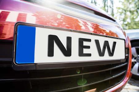 車に新しい単語を示すナンバー プレートのクローズ アップ 写真素材
