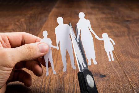 Close-up Of Person Cutting Family Papercut With Scissor At Wooden Desk