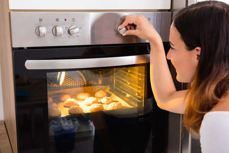 Young Woman Using Microwave Oven For Baking Fresh Cookies In Kitchen