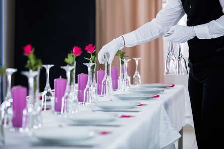 professional flute: Close-up Of Waiter Setting Wedding Table At Restaurant