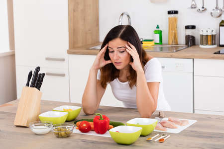 Young Unhappy Woman In Kitchen Near Different Ingredient