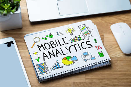 analytic: High Angle View Of Mobile Analytic Concept On Binder At Wooden Desk In Office Stock Photo