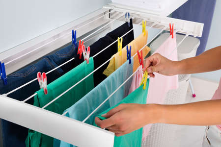 Close-up Of Woman Hanging Wet Clean Cloth On Clothes Line In laundry Room Foto de archivo