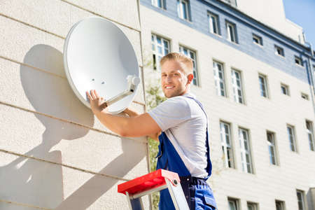 Young Man Fitting TV Satellite Dish To Wall 版權商用圖片