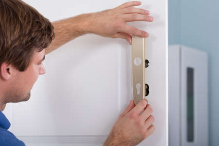 lock: Young Carpenter Installing Door Lock At Home Stock Photo