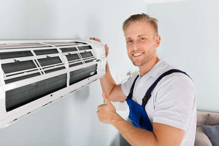 Lachende Man Elektricien gebaren thumbs up de buurt van Air Conditioner
