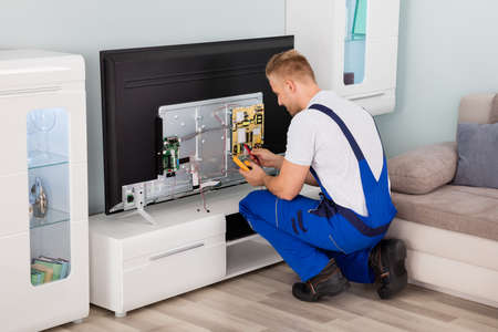 electrical appliances: Young Male Electrician In Overall Checking Television