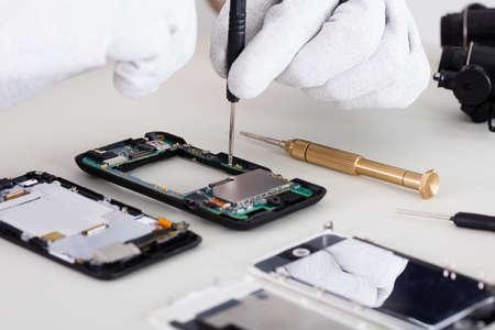 携帯電話の修復の手袋を身に着けている人の手のクローズ アップ