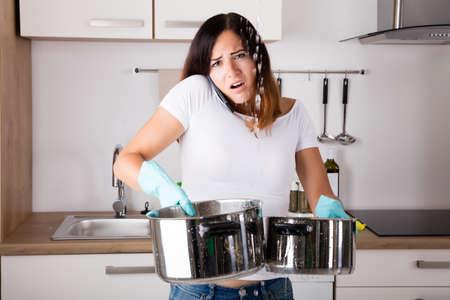 Geschokt Vrouw Die Plumber terwijl het verzamelen van water uit het plafond met behulp van gereedschap
