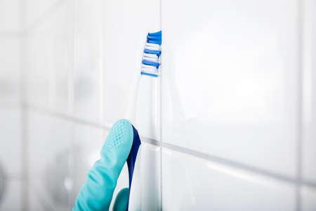 Primo piano della mano della persona che pulisce le mattonelle bianche sporche della parete facendo uso della spazzola Archivio Fotografico