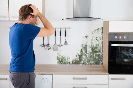 Jeune homme choqué en voyant mouler sur le mur dans la cuisine Banque d'images