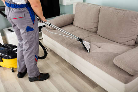 apartment cleaning: Rear View Of Young Male Worker Cleaning Sofa With Vacuum Cleaner Stock Photo