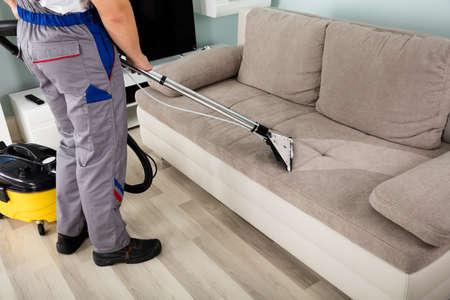 Vista trasera de trabajador masculino joven de limpieza en el sofá con la aspiradora