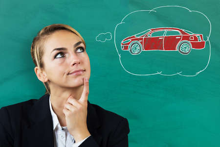 young businesswoman: Young Beautiful Businesswoman Thinking To Buy A Car Against Blackboard Stock Photo
