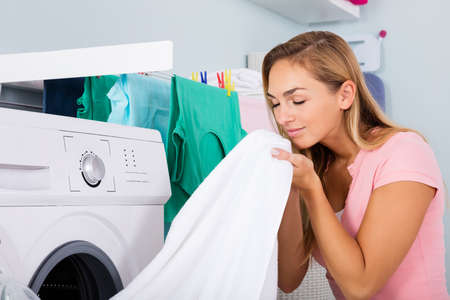 Woman Smelling Clean Clothes Near The Electronic Washer At Laundry Room