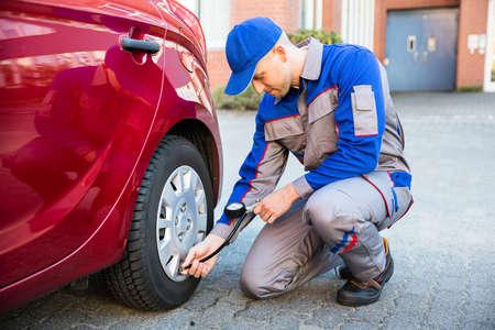Man Measuring Car Tyre Pressure With Pressure Gauge Stock Photo