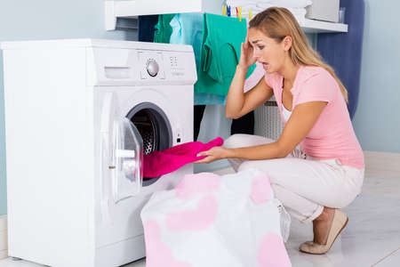 Shocked Angry Woman Looking At Bleached And Stained Cloth In Washing Machine At Laundry Room Stock Photo