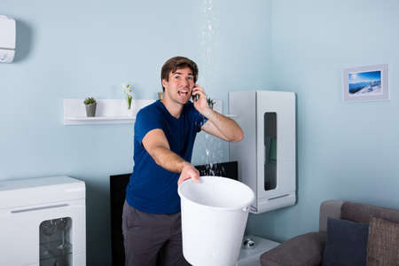 Worried Man Calling Plumber While Leakage Water Falling Into Bucket At Home Stockfoto