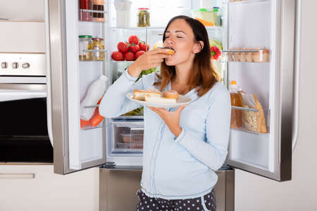 pregnant women donuts: Young Woman Enjoy Eating Donut From Plate Near Refrigerator In Kitchen