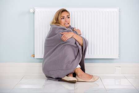 cold: Young Cold Woman Wrapped In Blanket Sitting Near Heater At Home