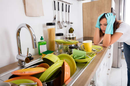 dirty: Tired Young Woman Standing In The Kitchen Looking At The Utensil In The Sink