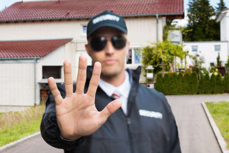 guard house: Confident Security Guard Making Stop Gesture Outside The House Stock Photo
