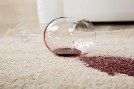 Veduta dall'alto di vino rosso versato dal vetro sul tappeto Archivio Fotografico