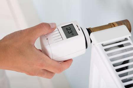 Ajuste de la temperatura de la mano de la persona en el termostato para controlar el calor En central Sistema de calefacción