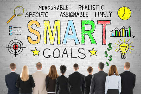 smart goals: Rear View Of Businesspeople Looking At Smart Goals Concept On Brick Wall