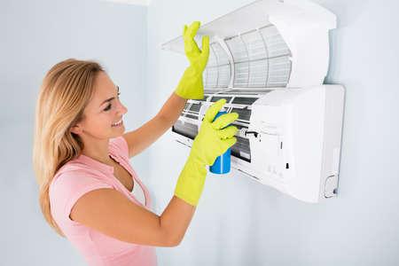 Limpieza del Aire Acondicionado de la mujer joven feliz con la botella de aerosol en el hogar