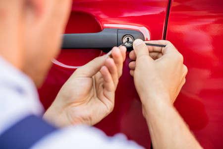 Lockpicker と車ドアを開ける人の手のクローズ アップ
