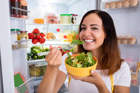 eating salad: Portrait Of Smiling Young Woman Enjoy Eating Salad In Front Of Open Refrigerator